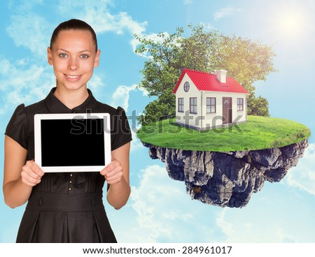 Businesswoman with tablet and house on island in the sky with clouds - stock photo