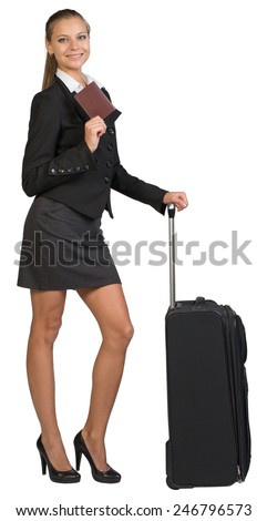 Businesswoman with wheeled travel bag, showing passport with blank cover, looking at camera. Isolated over white background - stock photo