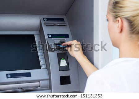 Businesswoman withdrawing money from credit card at ATM - stock photo