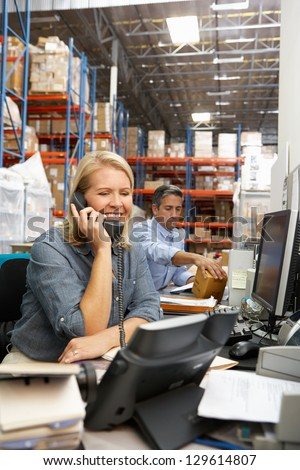 Businesswoman Working At Desk In Warehouse - stock photo