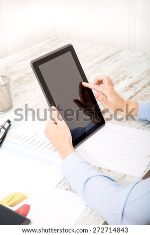 Businesswoman working at the office with the tablet and some documents - stock photo