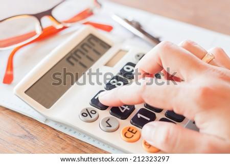 Businesswoman working in coffee shop with calculator, stock photo - stock photo