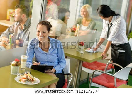 Businesswoman working in lunch break in cafe writing happy inspiration - stock photo