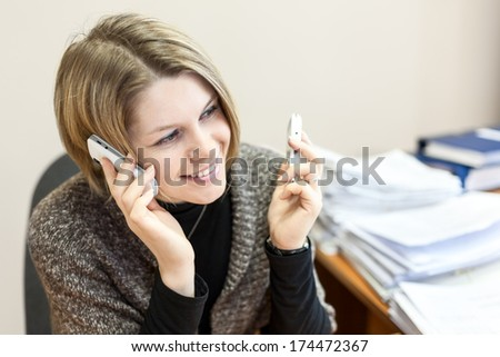 Businesswoman working in office and calling phones - stock photo