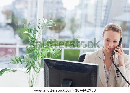 Businesswoman working on a computer with city view in background - stock photo
