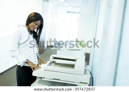 Businesswoman working on a copy machine at the office - stock photo