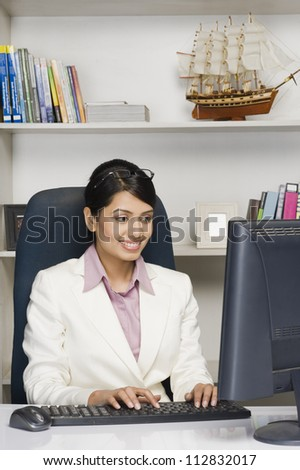 Businesswoman working on a desktop PC in an office - stock photo