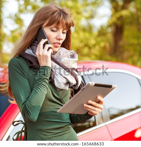 Businesswoman working on digital tablet while standing near the car outdoor - stock photo