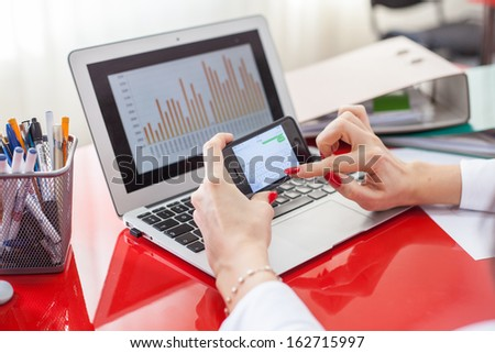 Businesswoman working on laptop in office. Close up of hands,laptop and mobile phone. - stock photo