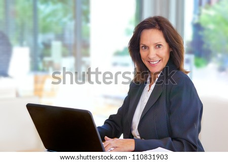 Businesswoman working with her laptop - stock photo