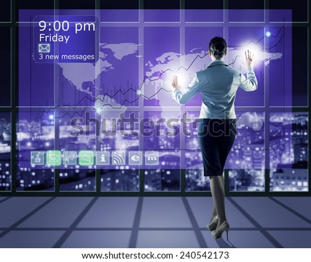 businesswoman working with modern virtual technologies, stands back, hands touching the screen - stock photo