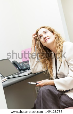 Businesswoman worried in office workstation looking up - stock photo