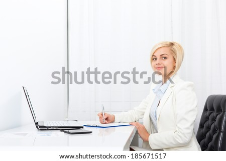 businesswoman writing contract, signing up paper document, business woman working sitting at modern white office desk - stock photo