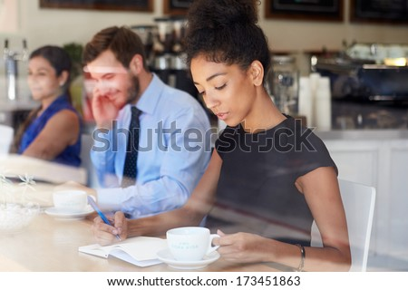 Businesswoman Writing Notes In Coffee Shop - stock photo