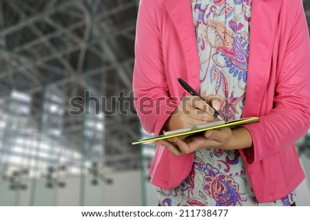 Businesswoman writing on clipboard in office room - stock photo