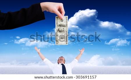 Businesswomans hand holding hundred dollar bill against snowy landscape under blue sky - stock photo