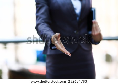 Businesswomans hand reaching out for handshake - stock photo