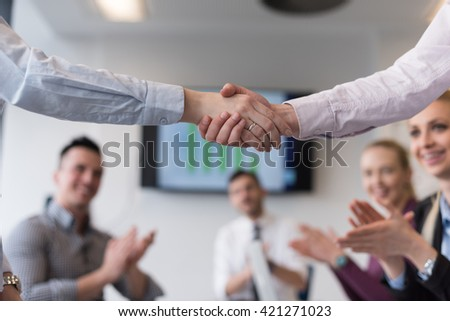 businesswomans handshake on team meeting  with group of people blured in background at modern startup business office interior - stock photo