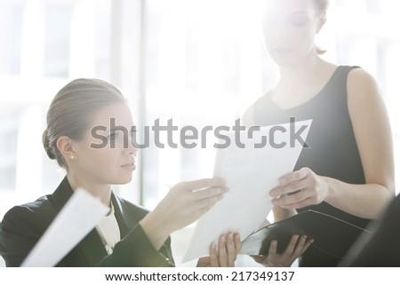 Businesswomen doing paperwork in office - stock photo