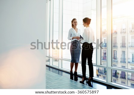 Businesswomen dressed in formal wear talking about work while meeting in hallway company, two female intelligent managers discussed plan the future conference while standing near big office window   - stock photo