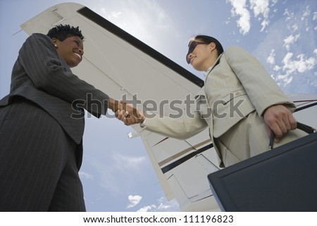 Businesswomen giving each other a handshake at the airport - stock photo
