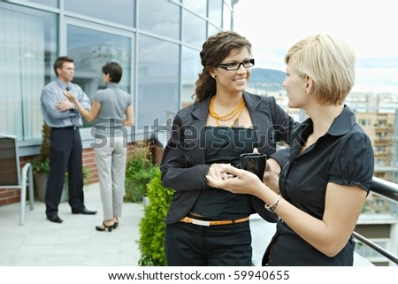 Businesswomen having break on office terrace outdoor drinking coffee talking. - stock photo