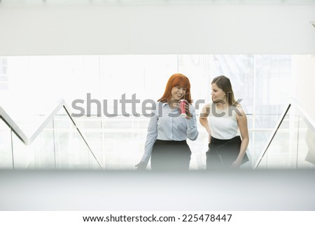 Businesswomen having coffee while moving up steps in office - stock photo