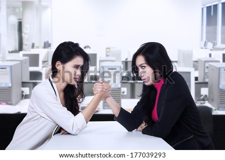 Businesswomen in arm wrestling gesture on working table during meeting - stock photo
