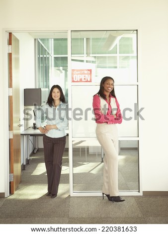Businesswomen smiling for the camera in office space - stock photo