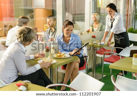 Businesswomen talking business in lunch break cafe happy working showing - stock photo