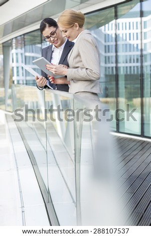 Businesswomen using digital tablet by glass railing - stock photo