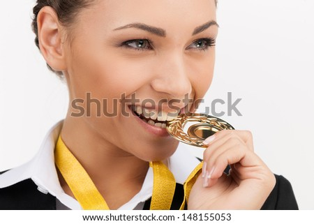 Businesswomen with gold medal. Beautiful young businesswomen trying her gold medal by teeth while isolated on white - stock photo