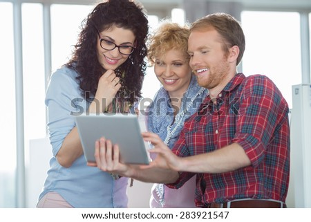 Businesswomen with male colleague using tablet PC in creative office - stock photo