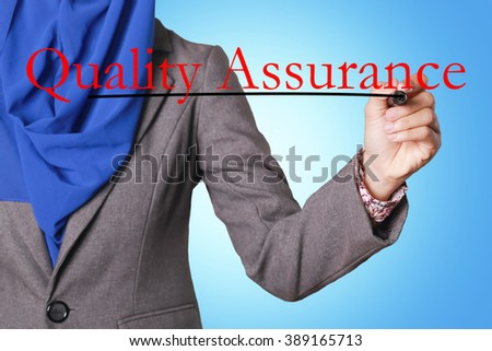 Businesswomen writing text Quality Assurance with pen - stock photo