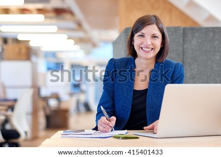 Busineswoman smiling broadly while working in her office cubicle - stock photo