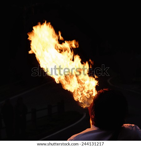 buskers fire-eater in the night - stock photo