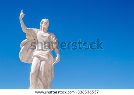Busko Blato, Bosnia and Herzegovina - July 2015 - A stone statue of prophet Elijah holding a knife or a sword and pointing to the Heavens, with bright blue sky in the background - stock photo