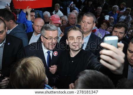 BUSKO ZDROJ, POLAND - MARCH 08, 2015: President of the Republic of Poland Bronislaw Komorowski during presidential election campaign, takes selfie with supporters - stock photo