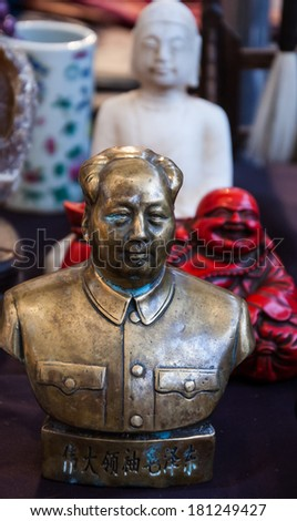 Bust of China's former Chairman Mao Zedong, red Laughing Buddha and white Buddha figurines at background. Still life at flea market in Paris (France). Contrasts in life idea. - stock photo
