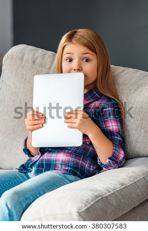 Busted with her touchpad. Beautiful little girl holding her touchpad and looking surprised while sitting on the couch at home - stock photo