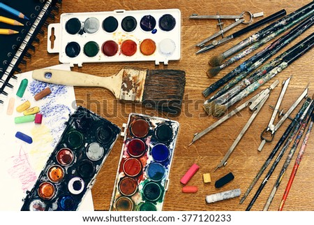 Busy artist's workplace. Large number of organized tools. Used and paintbrushes, number of watercolor sets, sketchbook, crayons, pastels, paper. Wooden table as a background. Drawing and scaling tools - stock photo
