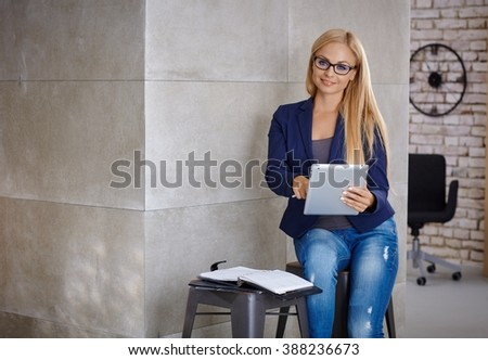 Busy blonde woman working with tablet, using personal organizer. - stock photo