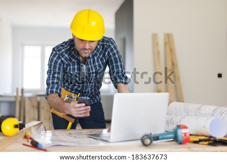 Busy building contractor at work  - stock photo