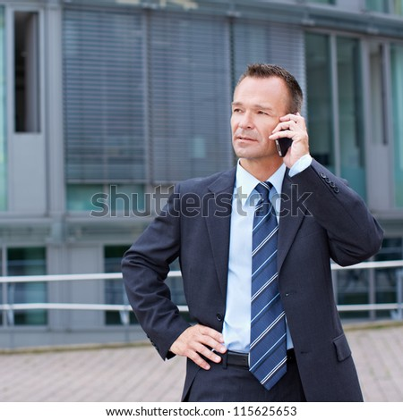 Busy business man using his smartphone to make a phone call - stock photo