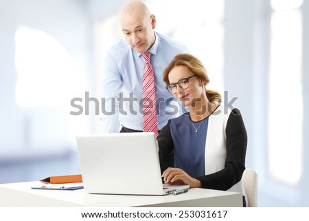 Busy business woman and businessman discussing business plan while sitting at office in front of laptop.  - stock photo