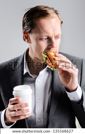 Busy businessman eating takeaway sandwich on the go, rushing through lunch break - stock photo
