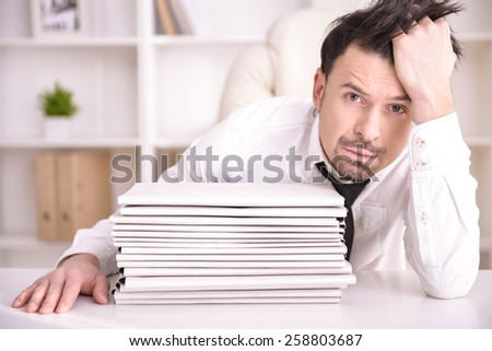 Busy businessman spectacled with a lots of folders - stock photo