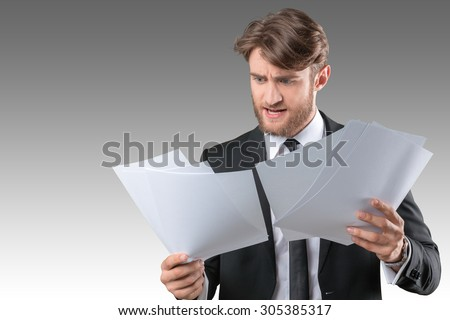 Busy businessman with loads of paperwork - stock photo