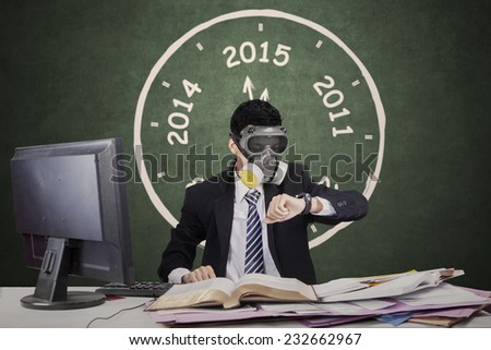 Busy businessman working in office while wearing a gas mask and looking at his timepiece - stock photo