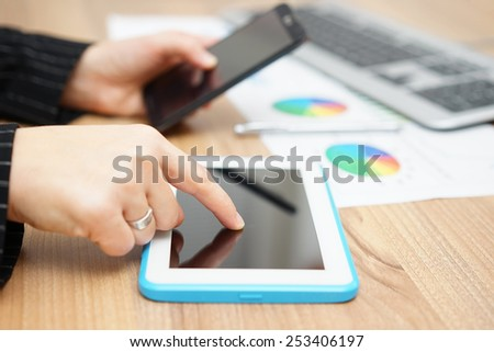 Busy businesswoman is working on tablet computer and using smart mobile phone - stock photo